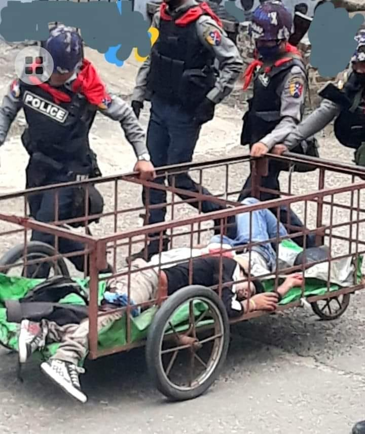 Police officers are seen transporting two bodies in a cart in Mogok on April 17 (CJ)