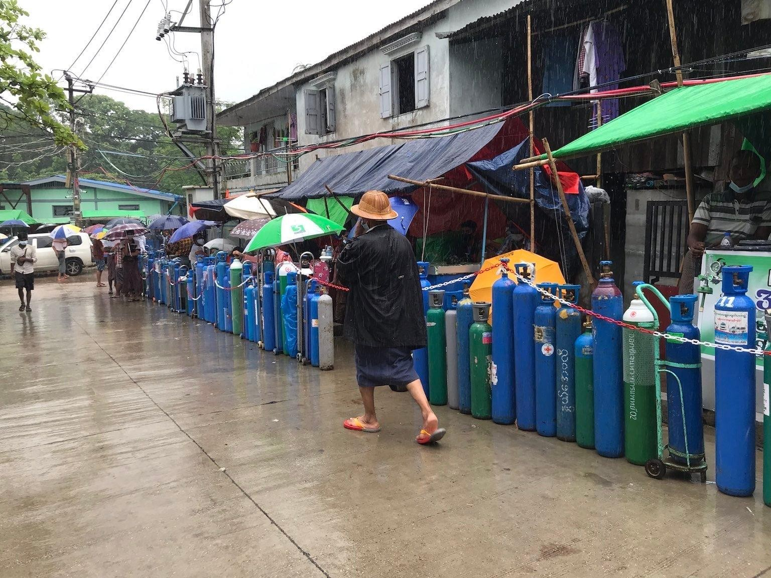 People queue in the rain for oxygen in front of the Nwe Aye Mosque in Yangon's Dawbon Township on July 12. (Photo: Myanmar Now)