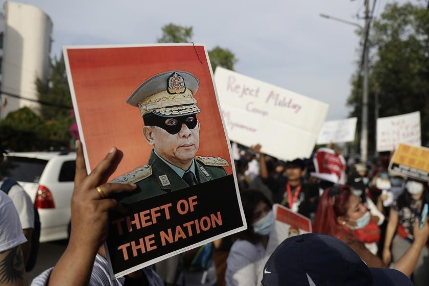 Demonstrators hold a placard depicting junta leader Min Aung Hlaing at a protest outside the Chinese Embassy in Yangon on February 12 (EPA-EFE)