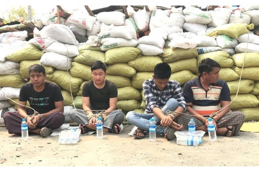 Four policemen detained by protesters are pictured at the Tarhan protest site on Bogyoke road in Kalay. (Supplied)